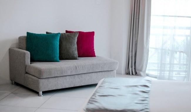 divano chiaro con cuscini di colore verde grigio e rosso