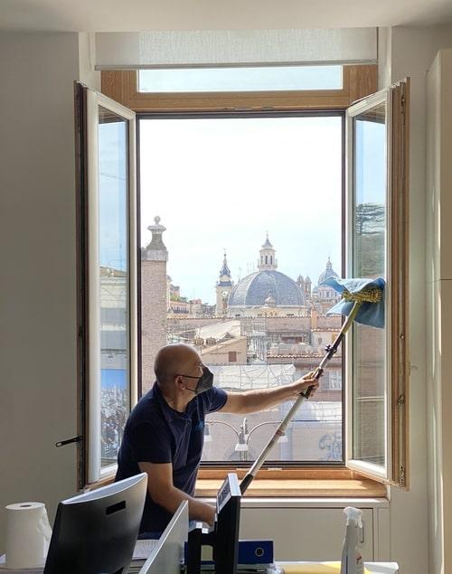 uomo che pulisce una vetrata a roma dipendente dell'azienda adrianea